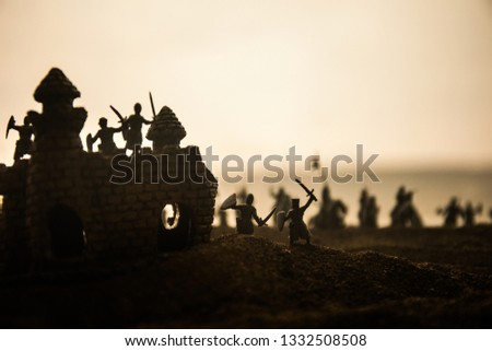 Medieval battle scene with cavalry and infantry. Silhouettes of figures as separate objects, fight between warriors on sunset foggy background. Selective focus #1332508508