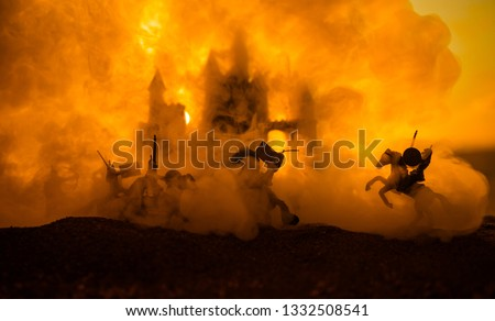 Medieval battle scene with cavalry and infantry. Silhouettes of figures as separate objects, fight between warriors on sunset foggy background. Selective focus #1332508541