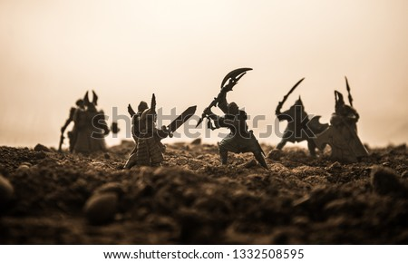 Medieval battle scene with cavalry and infantry. Silhouettes of figures as separate objects, fight between warriors on sunset foggy background. Artwork decoration. Selective focus #1332508595
