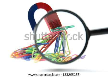 Magnet attracting a group of paperclips through magnifying glass