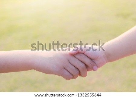 sister and brother holding hand in hand at the garden outdoor. #1332555644