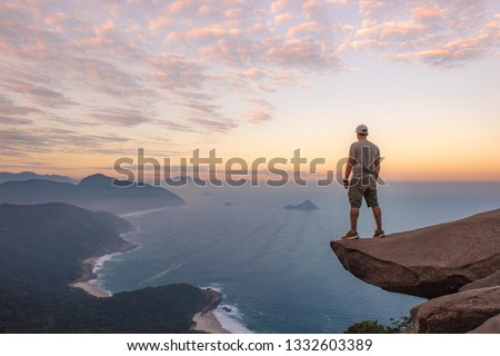Man on a rock precipice overlooking Rio De Janeiro's beautiful coastline at sunset. Hiking trail in Brazil, South America. #1332603389