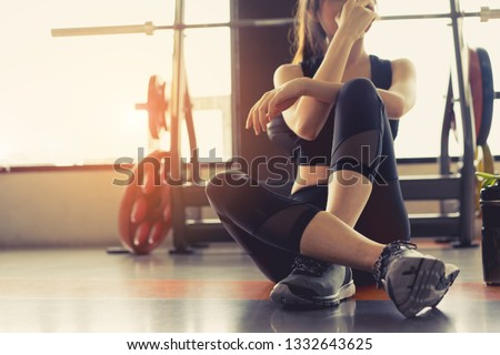 Woman exercise workout in gym fitness breaking relax holding apple fruit after training sport with dumbbell and protein shake bottle healthy lifestyle bodybuilding. #1332643625