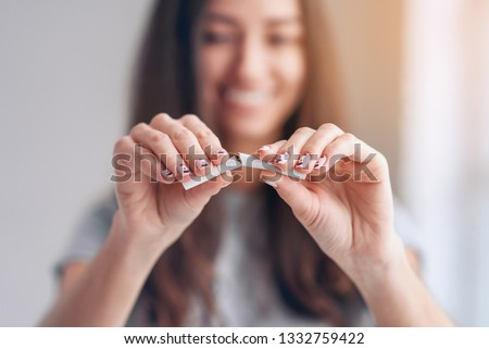 Stop smoking cigarettes concept. Close up of young smiling girl holds broken cigarette in hands. Happy female quitting smoking cigarettes. Quit bad habit, health care concept. No smoking. Tonned. #1332759422