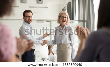 Happy manager boss praising old employee for good work get team appreciation acknowledgement handshaking successful worker congratulating promoting rewarding welcoming new partner, respect handshake #1332820040