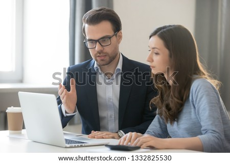 Helpful male boss mentor coach teacher explaining new online project to young female worker intern student, focused leader executive manager teaching student instruct trainee pointing at pc computer #1332825530