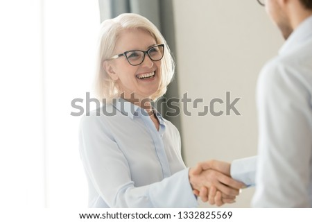 Happy older mature businesswoman shaking hand of male partner boss client greeting getting promoted rewarded, making business deal, respect, trust and gratitude handshake at business meeting concept #1332825569