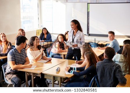 Female High School Teacher Standing By Student Table Teaching Lesson Royalty-Free Stock Photo #1332840581