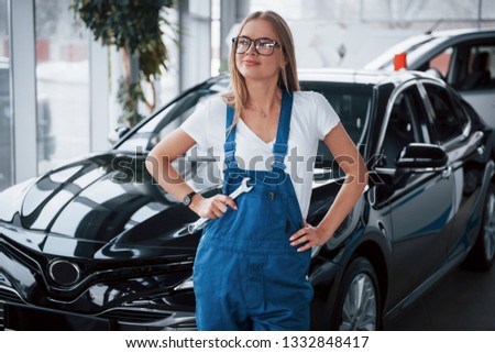 In joyful mood. Female repairer in the white shirt and blue uniform stands against new vehicles. #1332848417