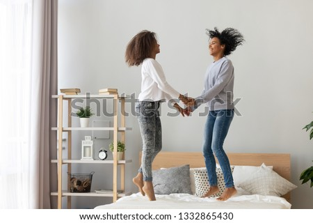 Mixed race mother and adolescent daughter holding hands jumping on bed, older sister or nanny playing having fun with pretty teen girl at home relative people enjoying spending time laughing together #1332865430