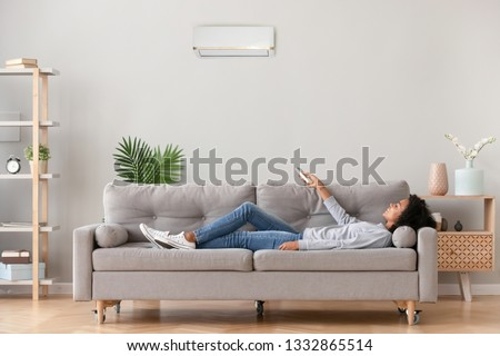 African relaxed woman in casual wear lying on sofa in living room at modern home holding air conditioner remote control, sets comfortable ideal optimal air degree temperature enjoy breathing fresh air #1332865514