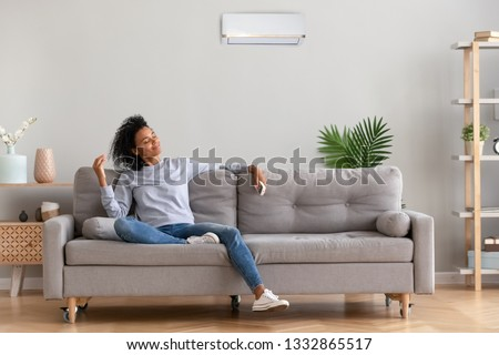 African american relaxed woman sitting on comfortable couch in living room at modern home holds air conditioner remote control enjoying breathing fresh cool air at summer or warm air at winter season #1332865517