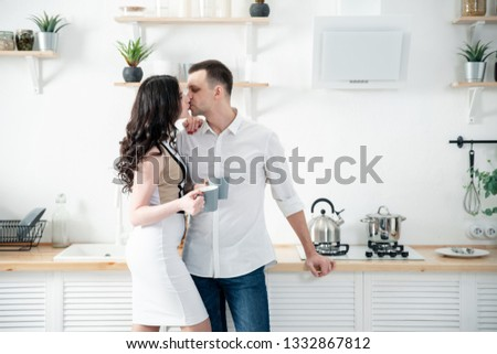 Loving couple. Girl and man in casual clothes in the kitchen. #1332867812