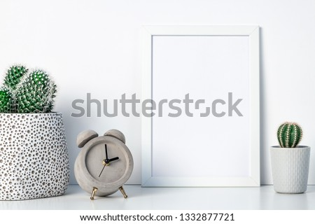 Shelf at home against a white wall. A mockup frame with space for text or graphics. Cactus decoration in pots. Scandinavian style. Concrete clock