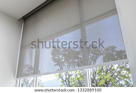 Roll Blinds on the windows, the sun does not penetrate the house. Window in the Interior Roller Blinds. Beautiful Blinds on the Window, the Sun and Heat Protection, the Perfect Windows Interior Decor #1332889100