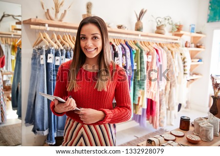 Portrait Of Female Owner Of Independent Clothing And Gift Store With Digital Tablet Royalty-Free Stock Photo #1332928079