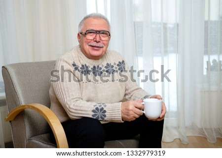 Happy and smiling senior man 70-75 years old in glasses sitting on the armchair and holding cup of coffee in hand on window background #1332979319