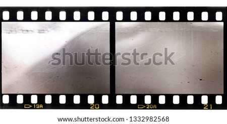 scratched 35mm film strip with two blank or empty frames #1332982568