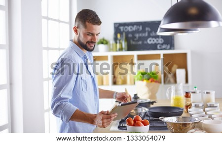 Smiling and confident chef standing in large kitchen #1333054079