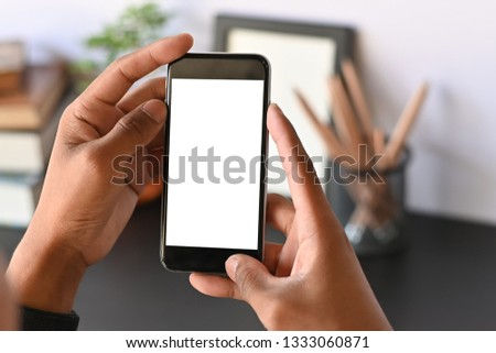 Cropped shot of smartphone on hands with empty screen on office desk. #1333060871