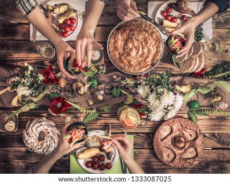 Traditional Easter celebration, Easter holiday party. Holiday friends or family at the festive table with rabbit meat, vegetables, pies, eggs, top view. Friends hands eating and drinking together. #1333087025