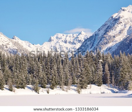 Beautiful winter at frozen snow covered alpine lake. Line of snow tipped evergreen trees. Heavy snow on Cascade Mountains under mostly blue sky. Mount Baker Snoqualmie National Forest in Washington. #1333186034