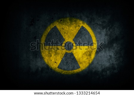 Nuclear energy radioactive (ionizing radiation) round yellow symbol shape painted on massive concrete cement wall grungy texture dark background. Nuclear radiation or radioactive alert concept. #1333214654