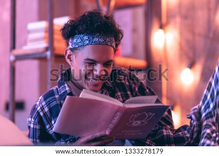 Kind of romantic. Embarrassed boy surprisingly candidly smiling to romantic story he reading in his favorite pink book. #1333278179