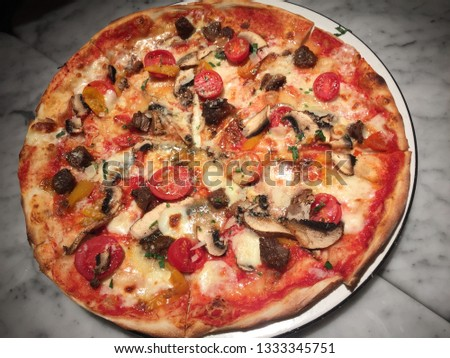 Close up of a delicious beef and tomato cheese pizza, Italian Food #1333345751