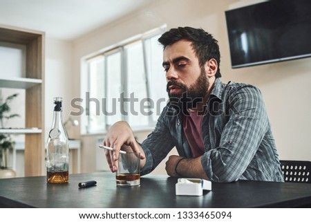 The first thing in the human personality that dissolves in alcohol is dignity. Alcohol abuse: drunk man lying down on a table with glass of whiskey still in hand #1333465094