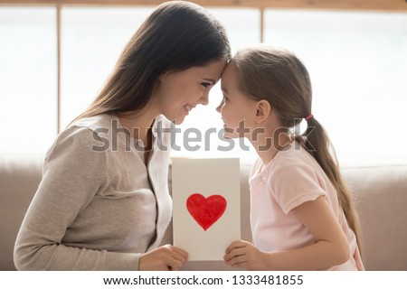Happy affectionate mom and cute little kid daughter holding greeting card with red heart touching foreheads bonding as concept of family love, mothers day congratulations, child mum care connection