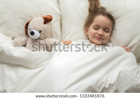 Happy cute baby girl sleeping with teddy bear toy in comfortable bed lay on pillow covered with warm blanket duvet, little kid fall asleep in bedroom, good night healthy child sleep concept, top view #1333481876