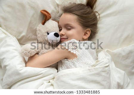 Cute little kid girl hugging teddy bear sleeping lay in cozy bed, happy small child embracing toy fall asleep on soft pillow white sheets covered with blanket having healthy night sleep, top view #1333481885