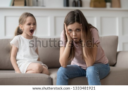 Stressed exhausted mother looking at camera feeling desperate about screaming stubborn kid daughter tantrum, upset annoyed mom tired of naughty difficult child girl misbehave yelling for attention #1333481921