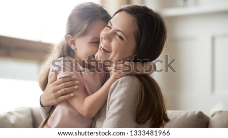 Loving young mother laughing embracing smiling cute funny kid daughter enjoying time together at home, happy family single mom with little child girl having fun playing feel joy cuddling and hugging #1333481966