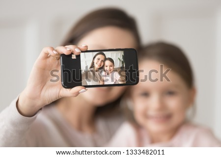 Happy young mother holding phone taking selfie on cellphone embracing child daughter, smiling mom and kid girl looking at smartphone camera making pic photo together, focus on mobile screen portrait