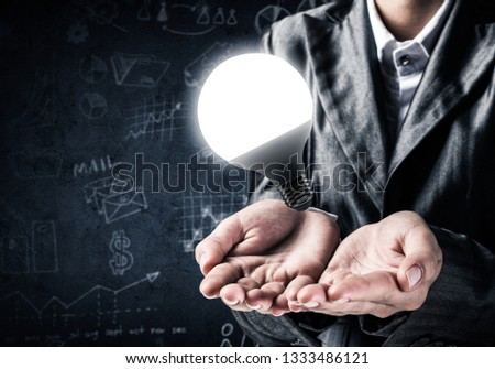 Businessman in suit presenting glowing lightbulb in hand as symbol of new idea, business sketches on background. 3D rendering. #1333486121