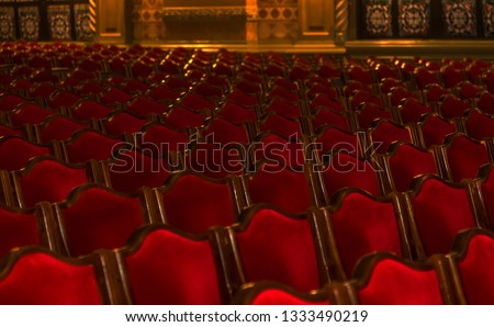 Interior theater art. Audience with empty soft armchairs of Opera and Ballet Theater is waiting for audience. Empty interior of concert theater before performance and without spectators. Soft focus #1333490219