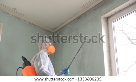 Mold remediation specialist in uniform inspects walls and spraying pesticide on damaged wall with sprayer #1333606205