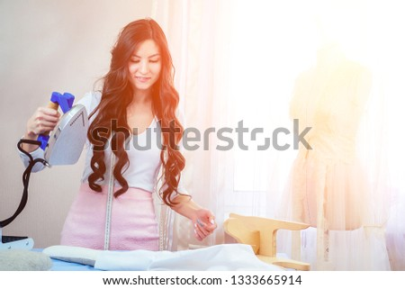 beautiful woman seamstress holds in her hand an electric iron. tailor sews a suit for the customer. dressmaker, mannequin and iron in the studio. wet-heat treatment of clothing in the sewing process. #1333665914