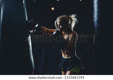Concept female sport. Strong athletic young blond woman is training self-defense punches in boxing gloves. #1333681394