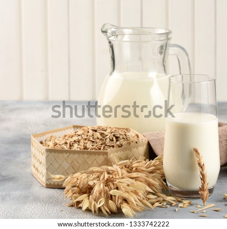 The concept of a vegetarian diet. Oat milk in the glass with jug of oat milk and oat and oat ears. Light background #1333742222