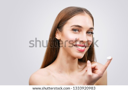 Beautiful young woman applying a creme on her face isolated on white background #1333920983