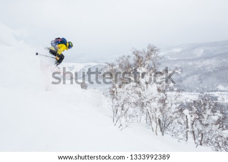 Backcountry skier jumps off a cornice near the summit of a small peak in backcountry Hokkaido, Japan. Yellow jacket, blue backpack powder skiing in Japan. Dropping off a cornice extreme skiing. #1333992389