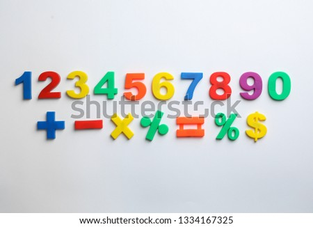 Colorful magnetic numbers and math symbols on white background, top view