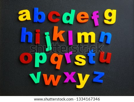 Colorful plastic magnetic letters on black background, top view. Alphabetical order