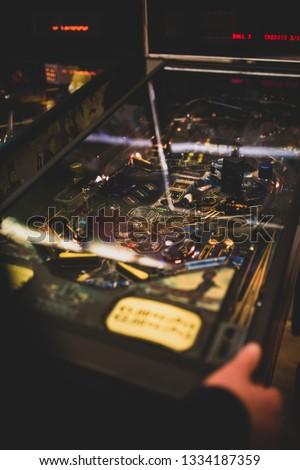 Man playing a pinball machine Royalty-Free Stock Photo #1334187359