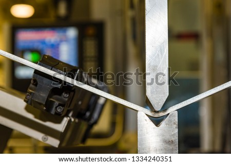 Hand robot working automatic cutting and bending metal sheet. operator bending metal sheet by sheet bending machine #1334240351