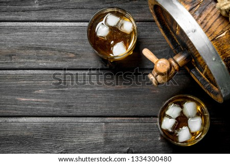 Whiskey in glasses with ice and a wooden barrel. On wooden background #1334300480