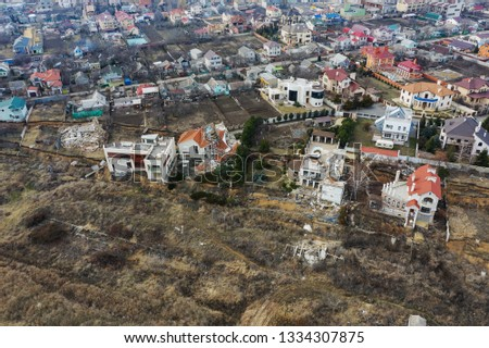 Landslide caused by rains of hurricane destroyed expensive cottages and houses. Destroyed house, cottage, large cracks, chips, slabs. Broken asphalt shifted landslide after earthquake. View from drone #1334307875